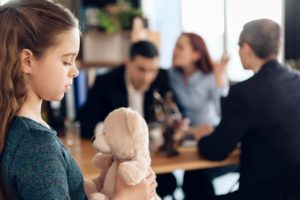 Girl holding her teddy bear while her parents are arguing at the background.