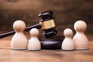 Separation of pawn wooden figure with gavel on wooden table In courtroom.
