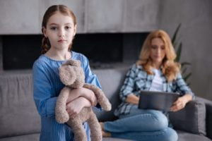 Sad girl holding her teddy bear while her mother is busy.