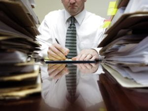 Man surrounded by stack of paperwork.