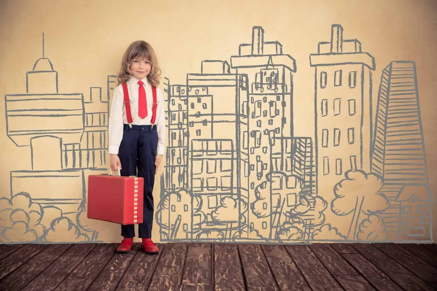 Little girl wearing tie carrying red suitcase in front of city.