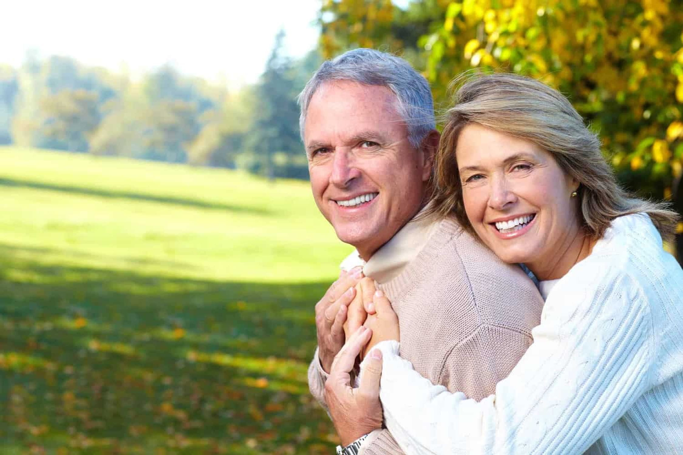 Older couple embracing in a park.