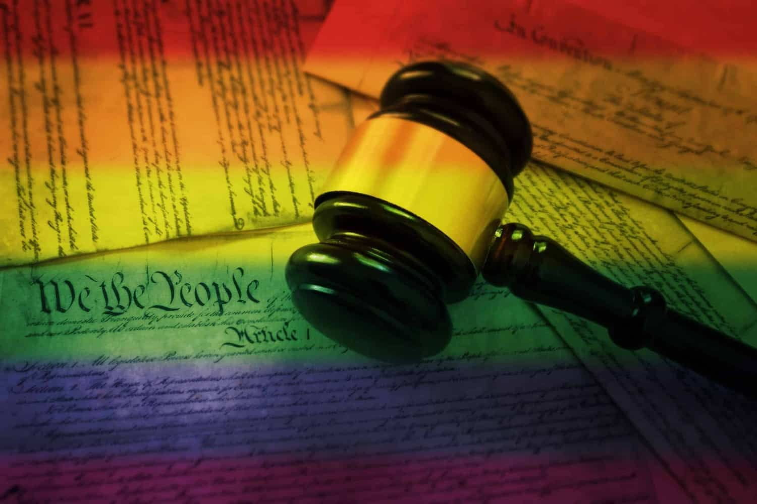 Judge's gavel on a rainbow-flag colored U.S. Constitution.
