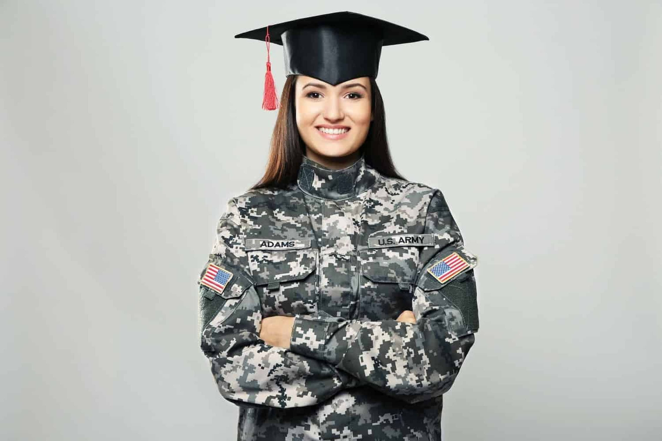 Female army soldier wearing graduation cap.