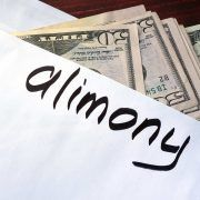 """Envelope filled with cash and """"alimony"""" written on the front."""