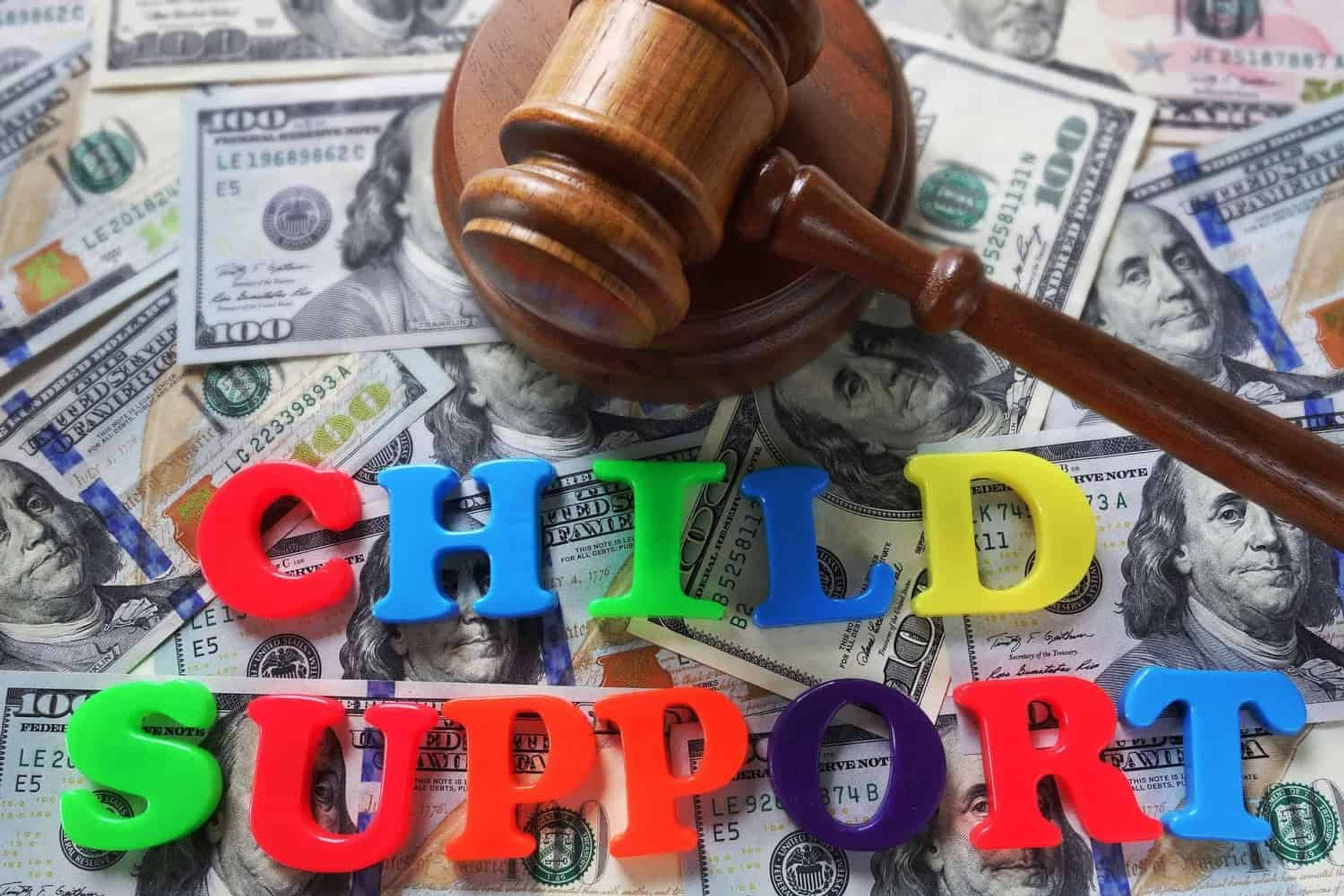 """Pile of $100 bills under a gavel with the words """"Child Support""""."""