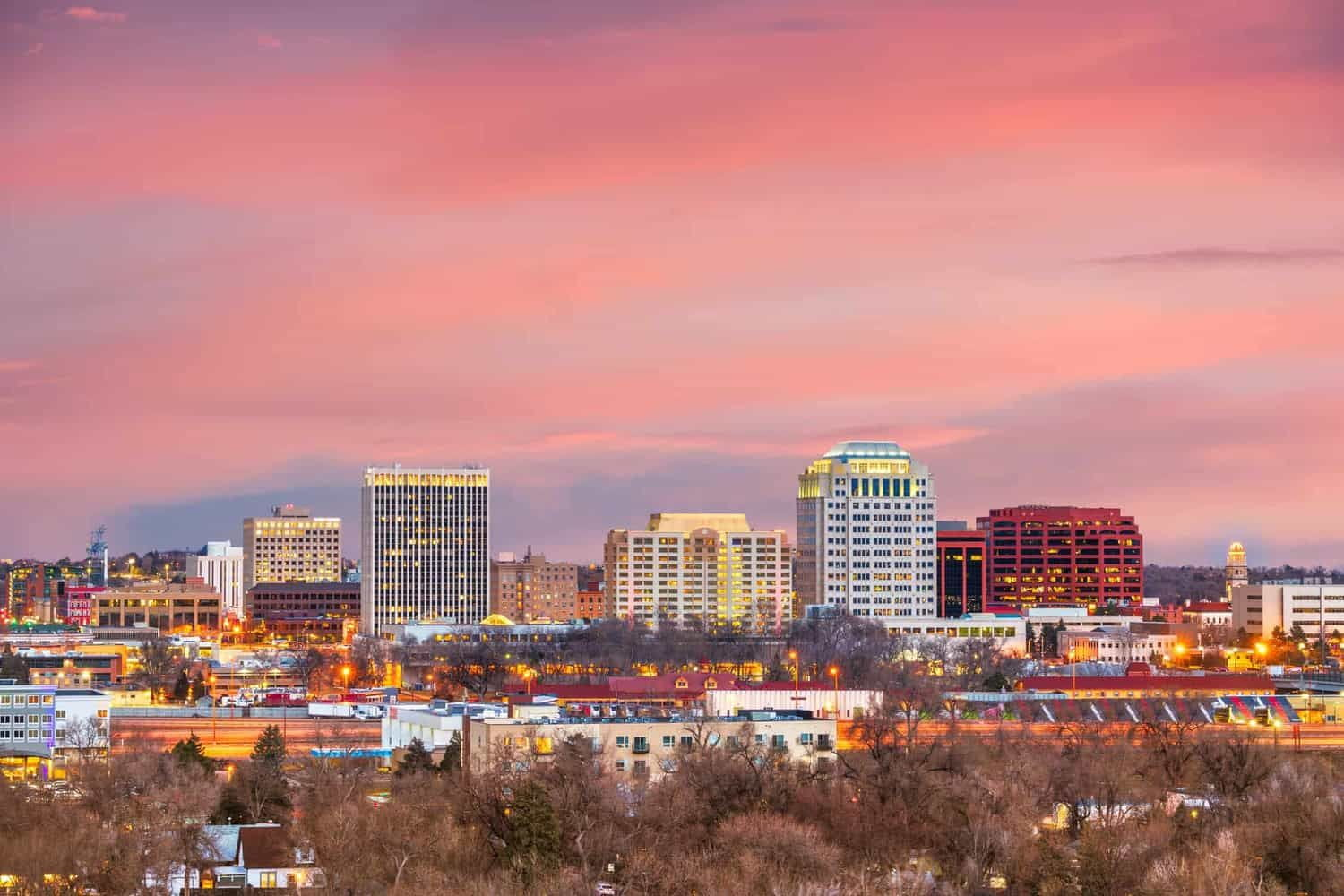 Colorado Springs city skyline & mountains at sunset.