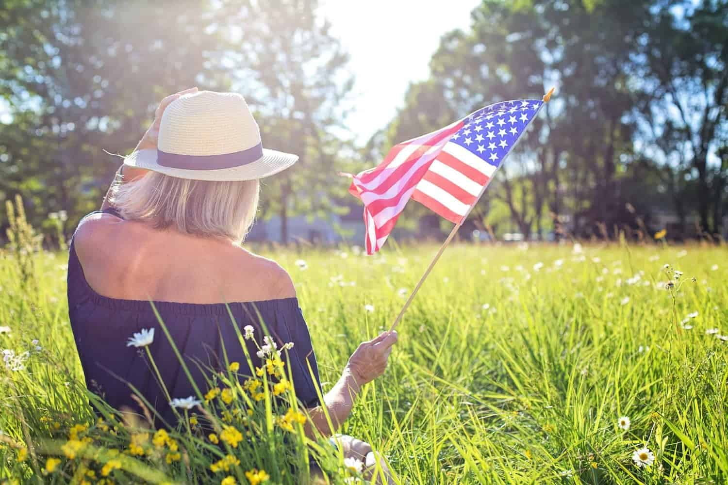 Woman sitting in field holding U.S. Flag