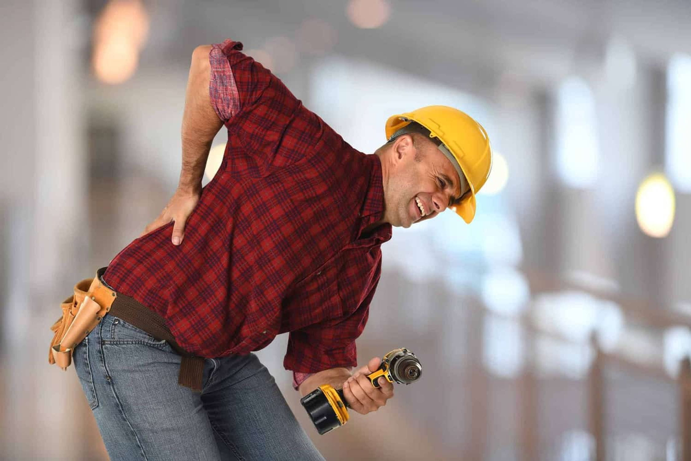 Construction worker holding drill who hurt his back.