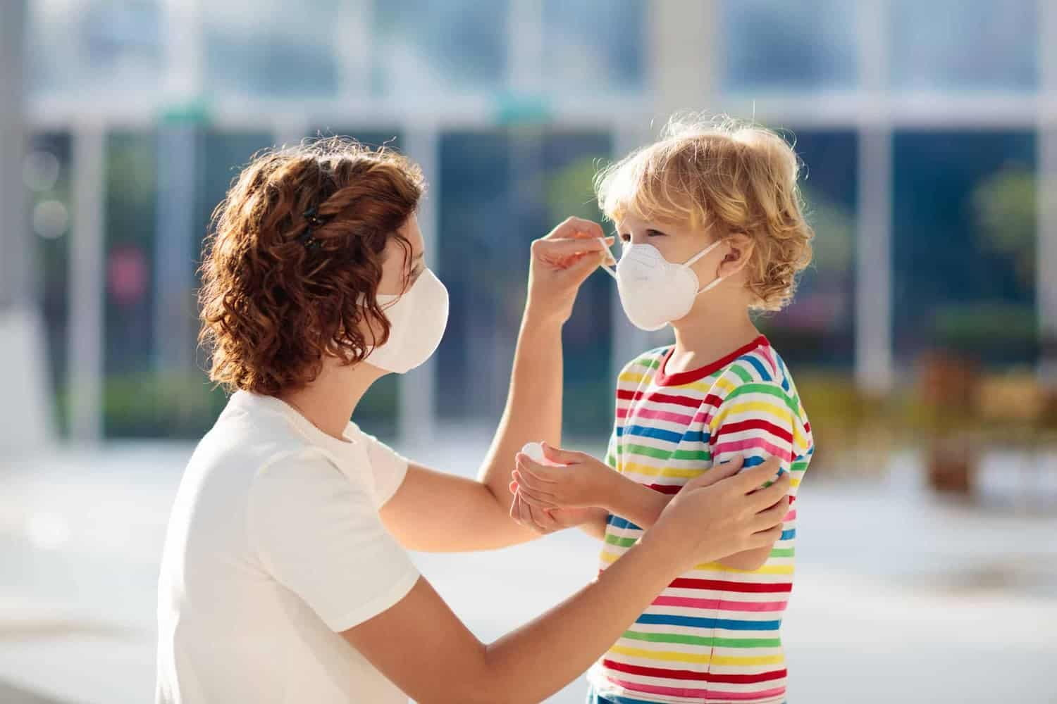 Mother fitting a medical mask on her young child.