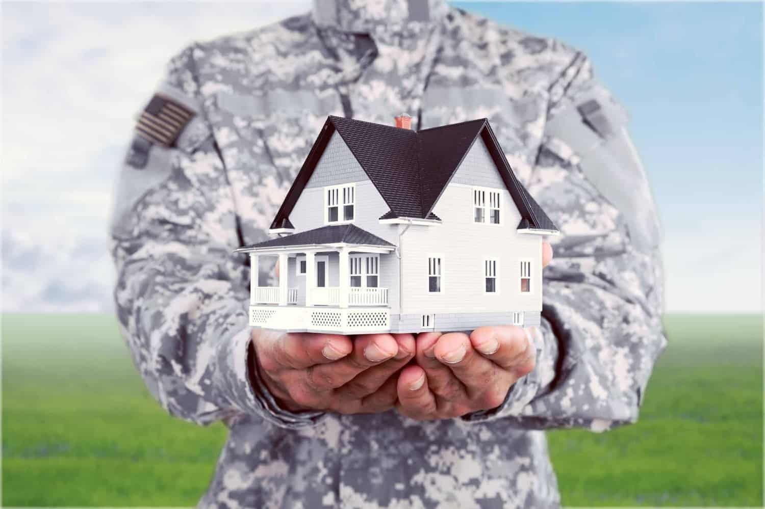 American soldier standing in field holding up a model house.