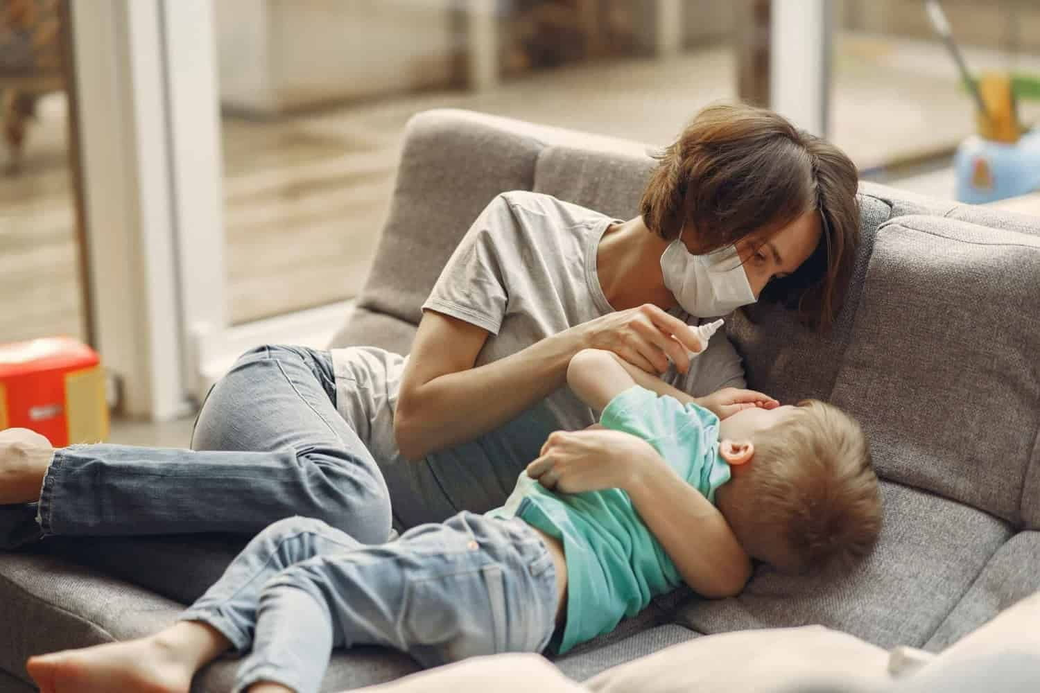 Mother wearing mask caring for child