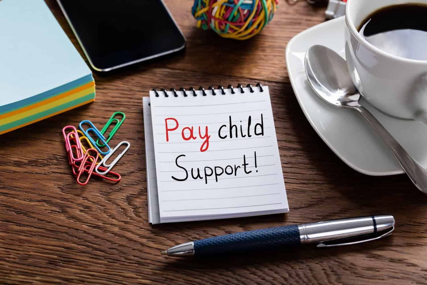 Desk with reminder note to pay child support.