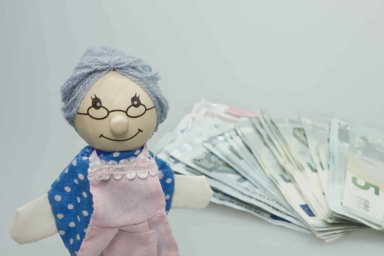 Doll of grandmother next to pile of money