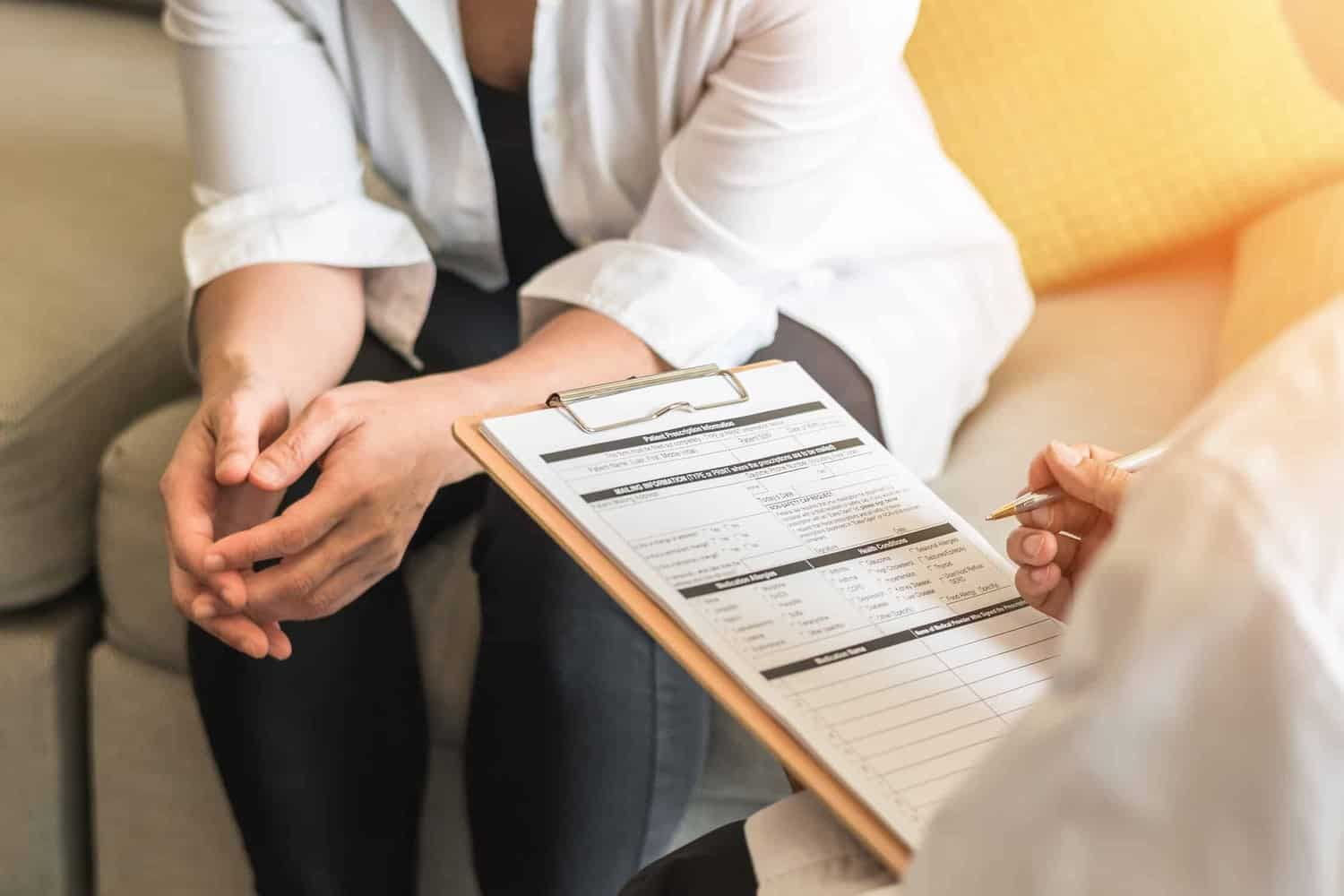 Therapist or doctor sitting on couch asking patient questions.