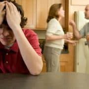 Upset teenage boy at table with parents arguing in background.