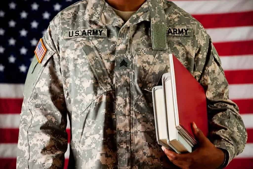 U.S. Army sergeant in front of American flag, carrying books.