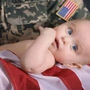 Military father holding baby wrapped in American flag