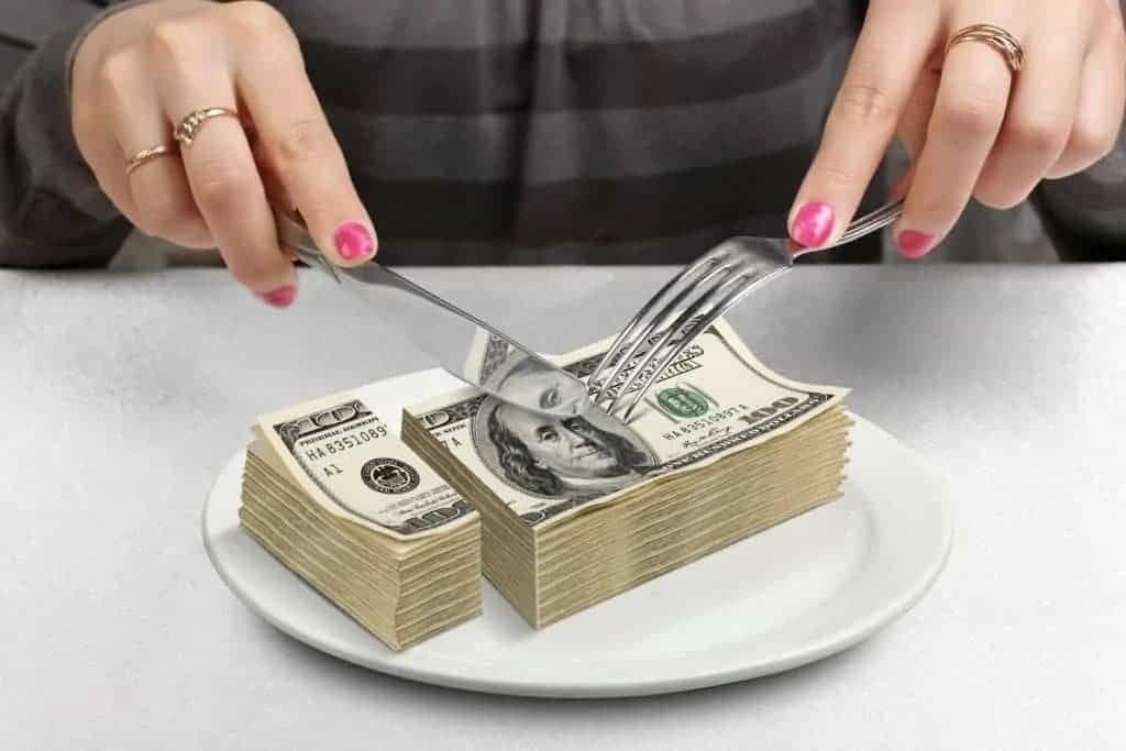 Person cutting stack of $100 bills with knife & fork.