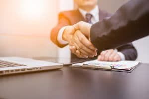 Two people shaking hands after reaching an agreement.