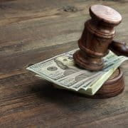 Judge's gavel with stack of $100 on top of it.