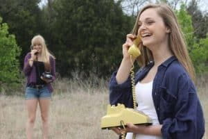 Two friends in a field talking on the telephone