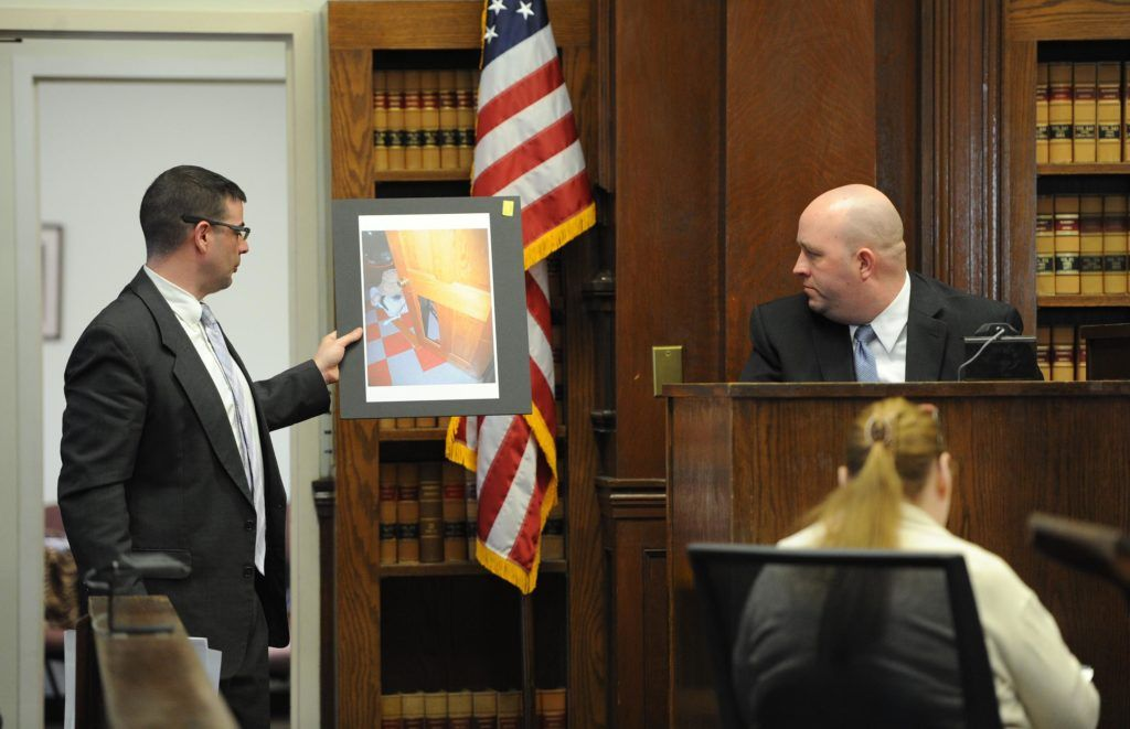 """From left, defense attorney Patrick Noonan, shows East Bridgewater police officer Peter Belmore, a photograph of the couples home a door panel leading into the laundry room that seemed to be kicked out. The trial for a former Boston firefighter accused of assaulting his wife began Tuesday in Brockton Superior Court.<br /> Richard R. Parker, who worked for the Boston Fire Department for nearly 26 years and was also a 9/11 responder, faces a charge of assault to murder amid others against his wife, Kimberly Boleza Parker, from an alleged incident in 2011. Parker died March 10, 2013 of causes that have not yet been determined.<br /> On Dec. 18, 2011, at 5 a.m., police responded to a 911 call placed from their Satucket Avenue home reporting that Parker was """"threatening his wife with a knife,"""" police logs show.<br /> In a written testimony following the incident, Kimberly Parker described a violent scene in which Parker was throwing knives at her while she stood pinned against a bedroom wall, according to court records.<br /> She was able to escape, she wrote, after one knife took a bad bounce and landed out of sight.<br /> Parker, 58, of 3 Satucket Ave., was indicted in 2012 following his wife's testimony in front of a grand jury. He is charged with kidnapping; assault to murder; assault with a dangerous weapon, a knife; threat to commit a crime and intimidation of a witness.<br /> Police, on two prior occasions before 2011, responded to the home for abuse reports.<br /> Kimberly Parker died March 10, 2013 at age 45 in her East Bridgewater home of causes that have not yet been determined.<br /> (Marc Vasconcellos/The Enterprise)"""
