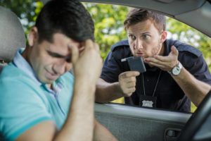 a cop checking a man for DUI with a Breathalyzer test