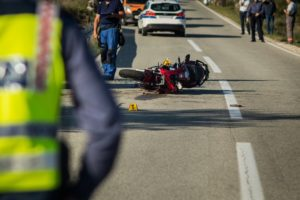 Car and a red sport motorcycle crash scene on an open road in afternoon.