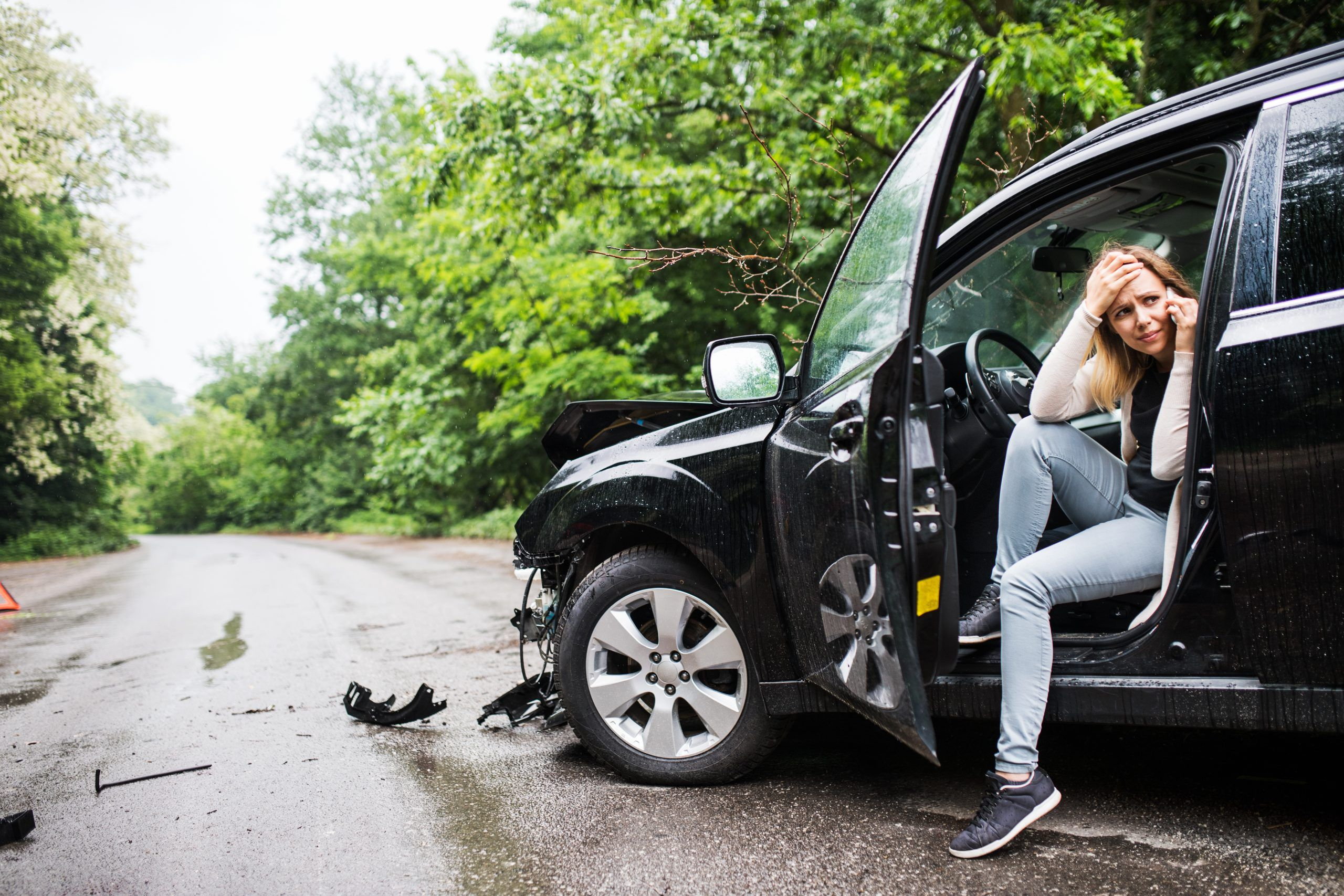 young woman in damaged car