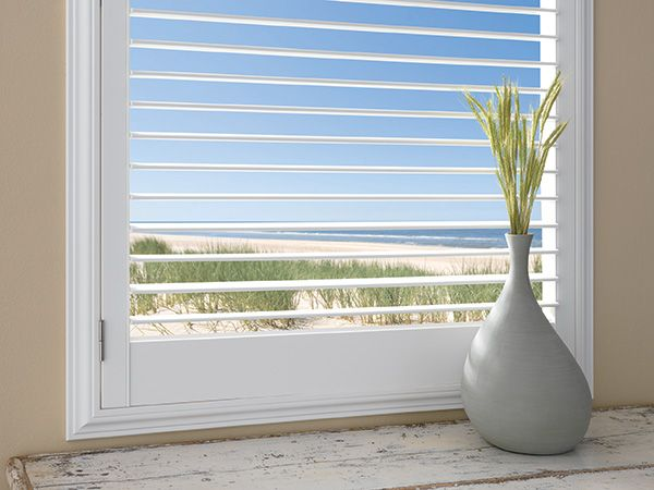 plantation shutters with a 2.5inch lourver by a shade above window fashions