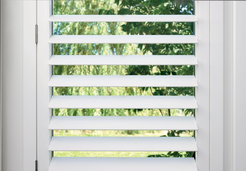 plantation shutters with hidden tilt bar by a shade above window fashions