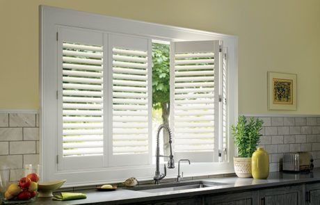 plantation shutters in kithen above sink by a shade above window fashions