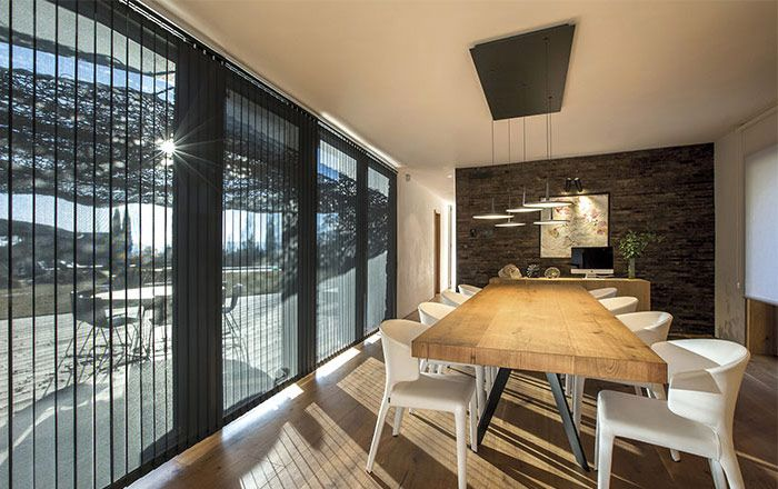 vertical blinds in dining room by a shade above window fashions