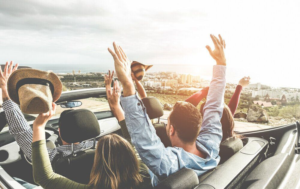 happy group of friends in a convertible car